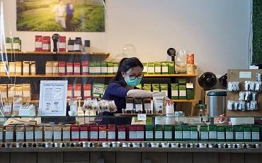 Shop worker at a deli counter arranging stock while wearing a face mask