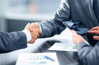 two people wearing suits and shaking hands