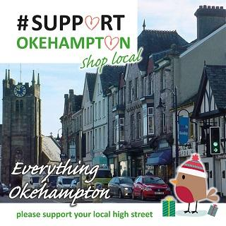 A photograph of Okehampton High Street with Christmas decorations and the message 'Support Okehampton'