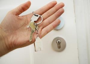 A hand holding a house door key