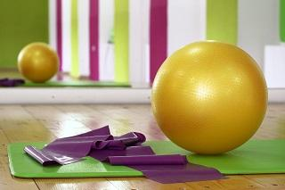 A yellow gym ball and purple yoga band arranged on a mat within a brightly painted exercise studio.