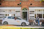 White electric car and electric bicycle with orange logo facing each other on street in front of shop windows